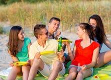Amis de sourire s'asseyant sur la plage d'été Photo stock