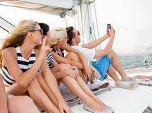 Amis de sourire s'asseyant sur la plate-forme de yacht Photos stock