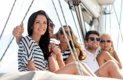 Amis de sourire s'asseyant sur la plate-forme de yacht Photo stock