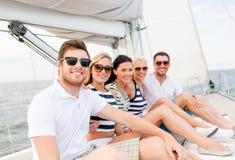 Amis de sourire s'asseyant sur la plate-forme de yacht Image libre de droits