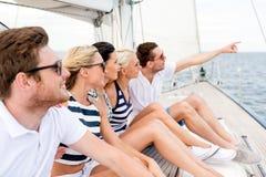 Amis de sourire s'asseyant sur la plate-forme de yacht Photos libres de droits