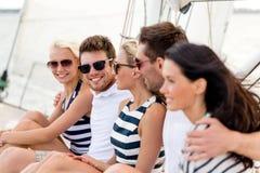 Amis de sourire s'asseyant sur la plate-forme de yacht Photo libre de droits