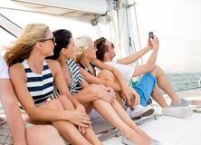 Amis de sourire s'asseyant sur la plate-forme de yacht Photographie stock libre de droits