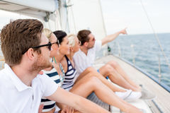 Amis de sourire s'asseyant sur la plate-forme de yacht Images stock