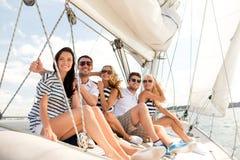 Amis de sourire s'asseyant sur la plate-forme de yacht Images libres de droits