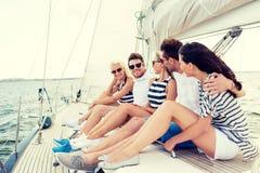Amis de sourire s'asseyant sur la plate-forme de yacht Photographie stock
