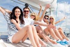Amis de sourire s'asseyant sur la plate-forme de yacht et saluant Image stock