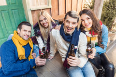 Amis de sourire s'asseyant sur le plancher et la bière potable Photo libre de droits