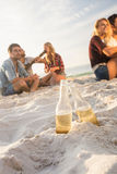 Amis de sourire s'asseyant sur le sable Photographie stock libre de droits