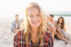 Amis de sourire s'asseyant sur le sable Photographie stock