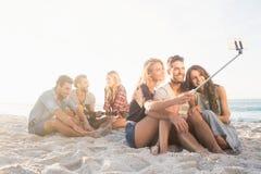 Amis de sourire s'asseyant sur le sable chantant et prenant des selfies Photo stock
