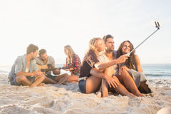 Amis de sourire s'asseyant sur le sable chantant et prenant des selfies Photo libre de droits