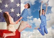 Amis de sourire sautant devant un drapeau américain Image stock