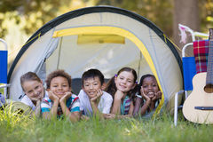 Amis de sourire se reposant dans la tente au terrain de camping Photos libres de droits