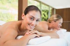 Amis de sourire se trouvant sur des tables de massage Image stock