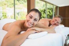 Amis de sourire se trouvant sur des tables de massage Images libres de droits