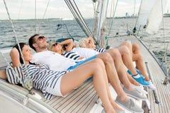 Amis de sourire se trouvant sur la plate-forme de yacht Photographie stock