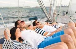 Amis de sourire se trouvant sur la plate-forme de yacht Photographie stock libre de droits