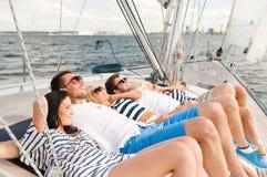 Amis de sourire se trouvant sur la plate-forme de yacht Image libre de droits