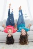 Amis de sourire se trouvant sur le sofa avec des jambes dans le ciel à la maison Images libres de droits