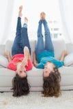 Amis de sourire se trouvant sur le sofa avec des jambes dans le ciel à la maison Image stock