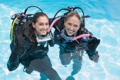 Amis de sourire sur la formation de scaphandre dans la piscine faisant le signe correct Image stock