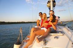 Amis de sourire sur la plate-forme et la salutation de yacht Images libres de droits