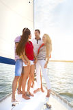 Amis de sourire sur la plate-forme et la salutation de yacht Image stock