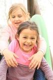 Amis de sourire sur une glissière Photographie stock