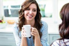 Amis de sourire tenant des tasses de café tout en se reposant à la table Photographie stock libre de droits