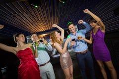 Amis de sourire tenant des verres de champagne et de vin tout en dansant Photo libre de droits