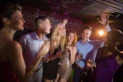 Amis de sourire tenant des verres de champagne tout en dansant Images libres de droits