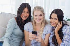Amis de sourire tenant le smartphone regardant l'appareil-photo Photographie stock