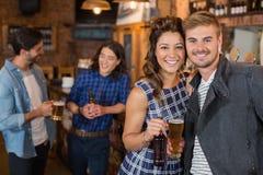 Amis de sourire tenant le verre et la bouteille de bière dans le bar Photographie stock