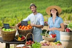 Amis de sourire vendant des fruits et légumes Photographie stock libre de droits