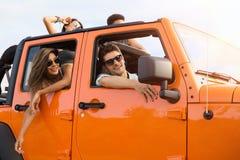 Amis de sourire voyageant ensemble en une voiture Photos stock