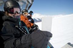 Amis de sport d'hiver dans l'ascenseur de chaise avec le billet Image libre de droits