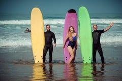 Amis de surfer sur une plage avec conseils surfants Photo stock