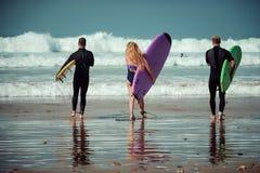 Amis de surfer sur une plage avec conseils surfants Image libre de droits
