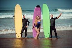 Amis de surfer sur une plage avec conseils surfants Images stock
