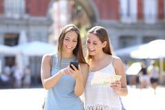 Amis de touristes consultant un guide en ligne Images libres de droits