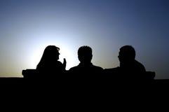 Amis de touristes parlant au coucher du soleil Images stock