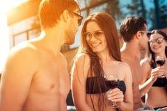 Amis de vacances d'été à la réception au bord de la piscine de natation Les jeunes passent le week-end dans la piscine Photographie stock