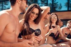 Amis de vacances d'été à la réception au bord de la piscine de natation La société des jeunes passent le week-end dans la piscine Images stock