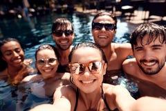 Amis de vacances d'été ensemble à la réception au bord de la piscine de natation Réception au bord de la piscine de natation images libres de droits