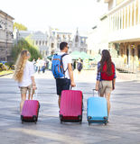 Amis de voyageurs avec le bagage marchant par la rue dans la ville Photo stock