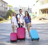 Amis de voyageurs avec le bagage marchant par la rue dans la ville Image stock