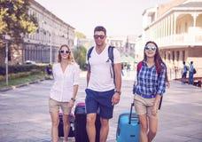 Amis de voyageurs avec le bagage marchant par la rue dans la ville Photos libres de droits