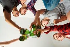 Amis de vue supérieure avec une bouteille de bière dans sa main, bott fait tinter Photo stock