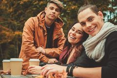 Amis derrière la table en bois en parc d'automne Image libre de droits